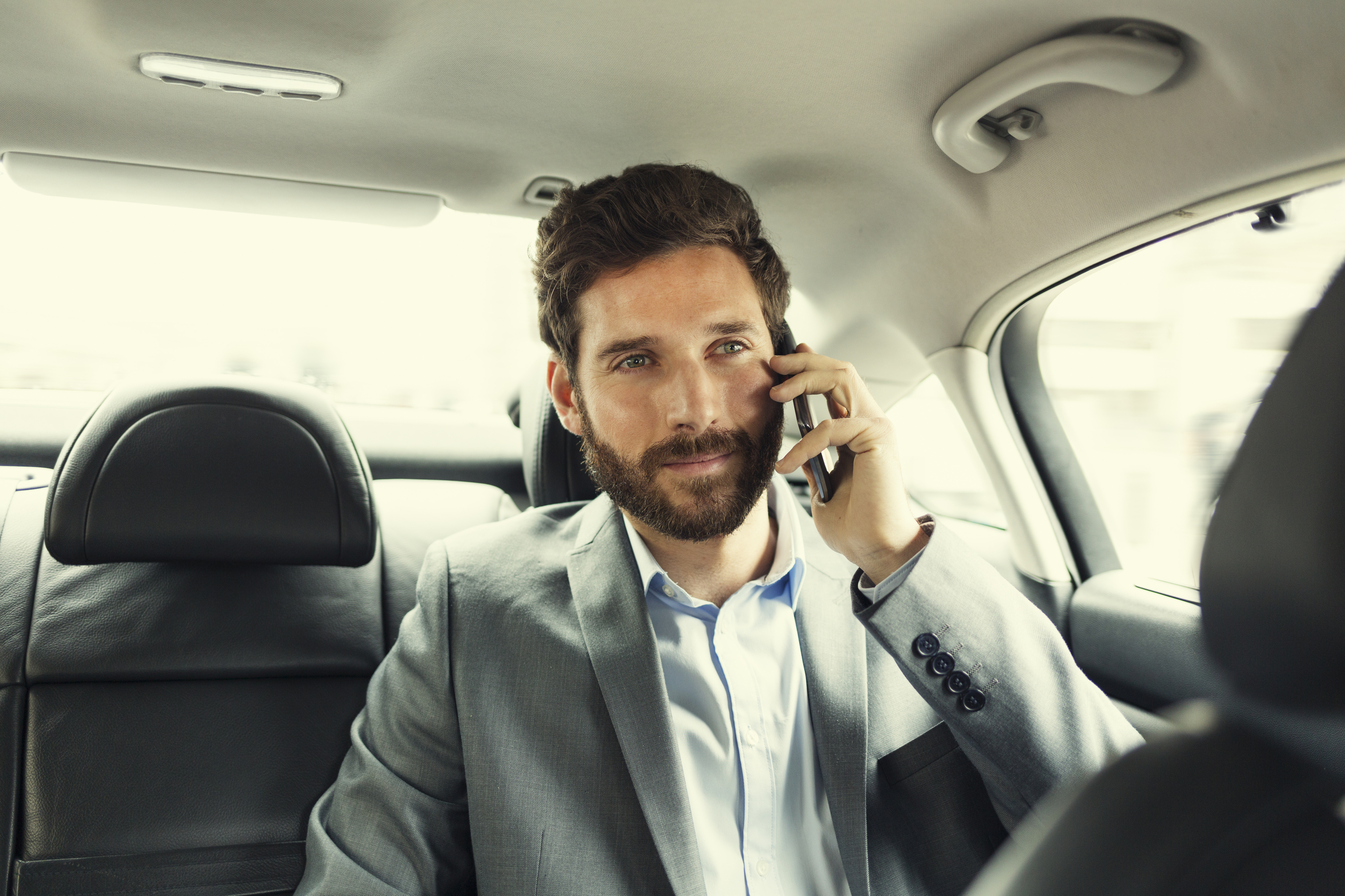 Casual business man on mobile phone in rear of car